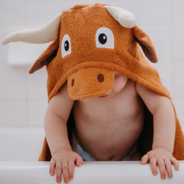 A toddler wearing a Yikes Twins longhorn steer hooded towel after a bath