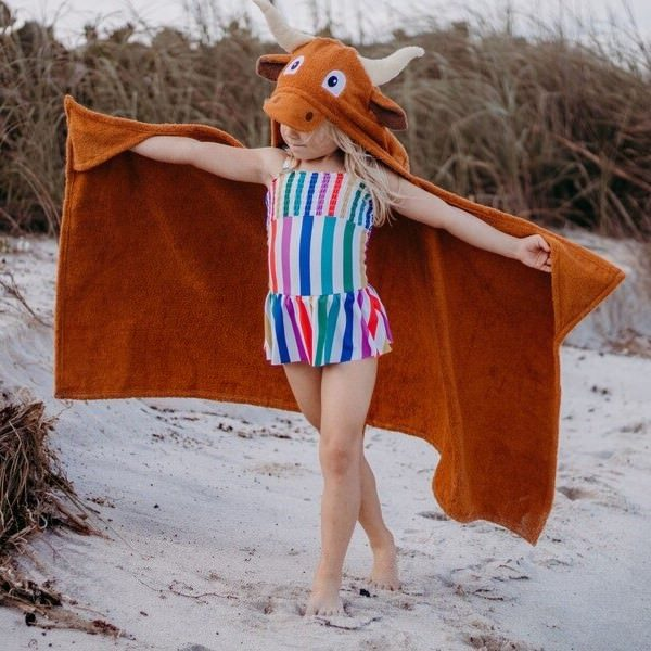 A child playing at the beach in their yikestwins longhorn hooded towel