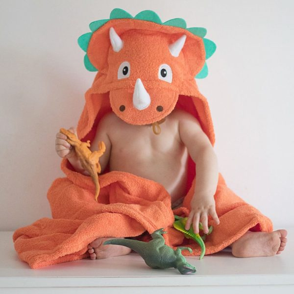 A toddler enjoying play time in their triceratops dinosuar hooded towel by Yikes Twins