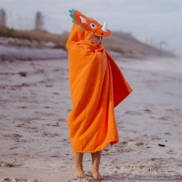 A kid wearing their dinosaur hooded towel at the beach