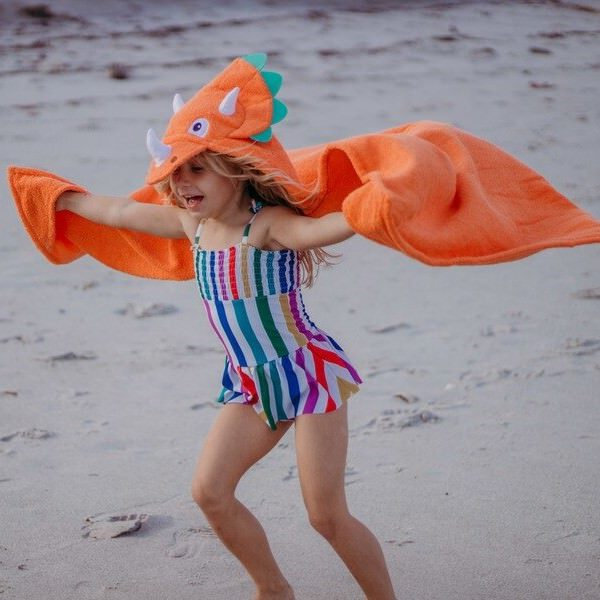 The Yikes Twins dinosaur hooded towel brings much fun to a toddler at the beach